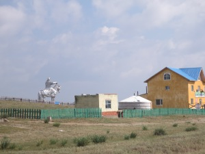 As we approach the gigantic statue, we see a combination of three different types of architecture: the traditional ger, the soviet-style minimalist concrete block house, and a more modern building under construction.