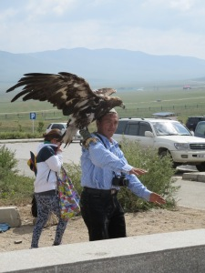 A Kazakh falconer dances to techno with his golden eagle, trying to lure customers into paying for a photo with the massive bird!