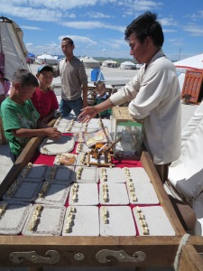 "A traditional Mongolian pastime, ""Bone games."" Using four horse vertebrae, the player rolls his hand and somehow ""races them,"" according to my host at least. I'm still waiting to learn the rules."