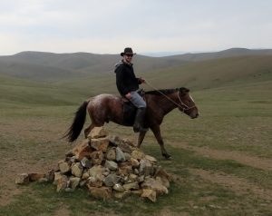 "Circling a ""odoo"" on my quarter horse. These sacred rock piles are meant to be circumambulated three times in a clockwise motion. It's a practice to pay respect to the spirits of the mountains and valleys and is generally observed by rural Mongolians."