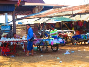 "Vendors sell snacks for travelers. After arriving at one small village, sticky rice, roasted chickens, and small beef sticks were thrust into the ""song-tu"" from all sides by local hawkers! I had no choice but to try the coconut rice (it was practically in my mouth already after being shoved into my face). Roasted in a hollow bamboo stalk it was delicious but too messy to even get a photo!"
