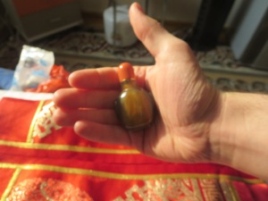 The proper way to hand off a snuff bottle, with the silk pouch in the background.