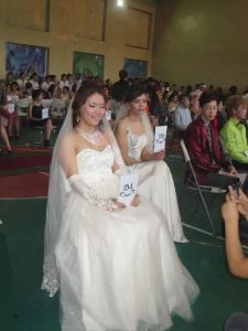 Bridal makeup and hair models sit with numbered cards, posing for photos and judges.
