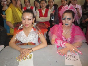 Outfits are as creative and ridiculous as the nail art itself. Competitors await the judges decisions in the background.