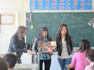 Students give a short presentation their peers  using a poster-sized picture.