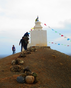 A child on his fathers shoulders places a rock on a stupa.